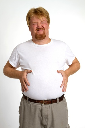 Overweight man with indigestion from overeating holds his stomach with discomfort and pain.