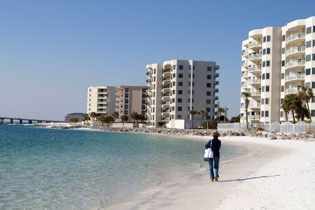 rentals: Mature female tourist walks along the beach in front of condominiums at Destin, Florida.