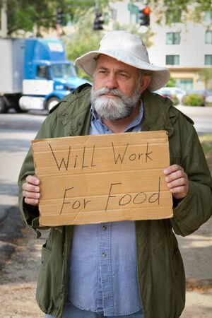 Homeless veteran begging at the side of the road holding a sign that says, Will Work For Food. Banco de Imagens