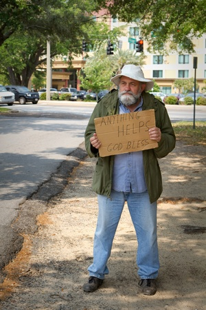 old beggar: Disheveled homeless man stands by the side of the road begging for help by holding a sign. Stock Photo