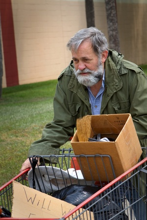ホームレスの男性は、古い軍隊のコートを着て彼の財産を保持しているショッピングカートをプッシュします。 写真素材