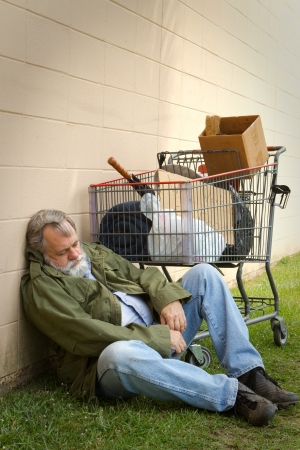 Homeless man leans against a wall sleeping with a grocery basket next to him containing his belongings. Stock Photo
