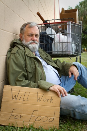 Homeless man rests leaning against a wall hold a sign with his possessions in a grocery cart.