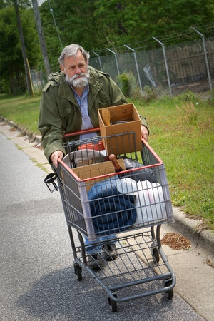 needy: Homeless Vietnam veteran pushes a shopping cart containing his possessions down the side of the street. Stock Photo
