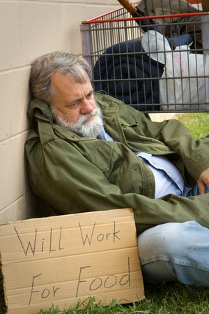 Homeless and hopeless man in an old army jacket waits for a handout. Stock Photo