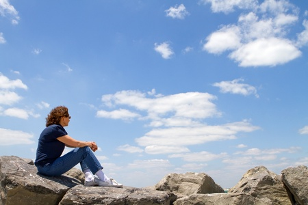 gazing: Meditating sixty year old mature woman sits on rocks and gazes out into a cloudy blue sky.