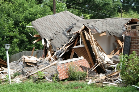 damaged roof: Ruins of an old house crushed by a tree in a wind storm.