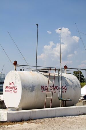 storage: Above ground fuel storage tank located at a boat marina with no smoking painted on the sides. Stock Photo
