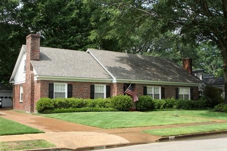 middle class: Americana de clase media casa de ladrillo en un barrio suburbano con bandera estadounidense con el aspersor de riego del césped.
