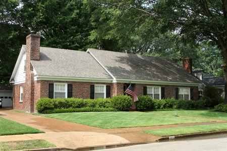 Middle class American brick home in a suburban neighborhood flying an American flag with the lawn sprinkler watering the grass. photo