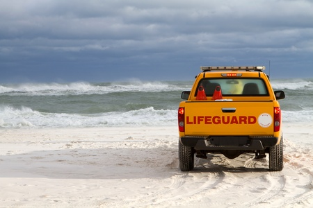Lifeguard stands in front of his vehicle to warn swimmers about the dangerous surf conditions during tropical storm generated waves in the Gulf of Mexico, on the Florida coast. photo
