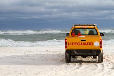 camioneta pick up: Salvavidas se pone delante de su vehículo para advertir a los bañistas sobre las condiciones peligroso oleaje durante las olas de tormenta tropical generada en el Golfo de México, en la costa de Florida.