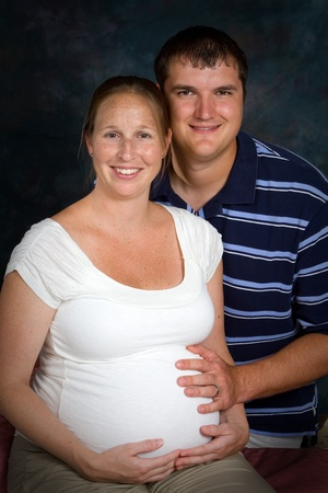 Expectant couple in a formal portrait photography session with the woman exhibiting the mask of pregnancy.