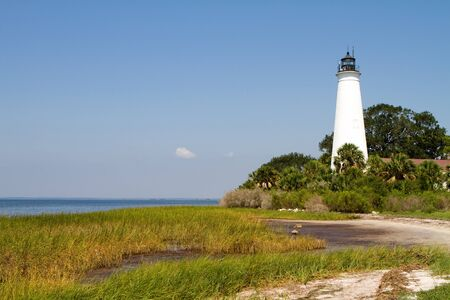 sawgrass: Floridas St. Marks Lighthouse on the Gulf of Mexico coast against a blue sky.