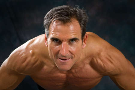 graying: Close pose of athletic adult male exercising by doing push-ups against a dark background.