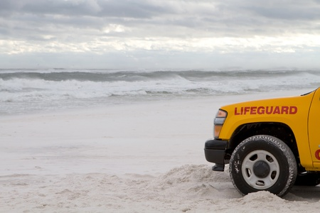 ashore: Lifeguard truck is parked on the beach as tropical storm generated waves come ashore to warn swimmers about the dangerous surf.