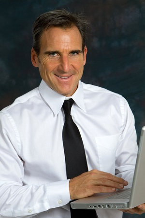 Happy smiling mature businessman, wearing a white shirt and tie, holds a laptop computer and smiles. Stock Photo - 10747506