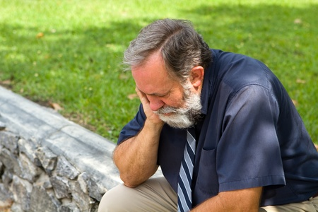 Businessman depressed by economic conditions sits melancholic in a park with his head in his hand.