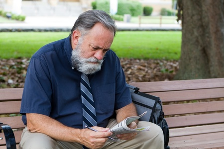 Unemployed middle aged man looks at advertisements for jobs in a newspaper while sitting on a park bench. Imagens
