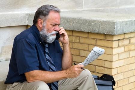 Oudere werklozen verkoper doet een oproep op zijn mobiele telefoon te antwoorden op een advertentie voor een job gevraagd-advertentie in de krant. Stockfoto