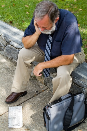 Older mature unemployed office worker sits distressed after viewing the want ads for a job.