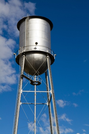 Old retro style water tower that has been restored and painted against a blue sky. Sirens are attached and used as a community alert system. photo