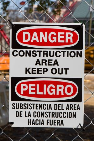 bilingual: Bilingual sign in both the english and spanish language for minorities warns to keep out because of danger in a construction area is attached to fence. Editorial