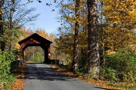 Wooden covered bridge in autumn crossed Owens Creek on Roddy Road in Frederick County, Maryland, USA.