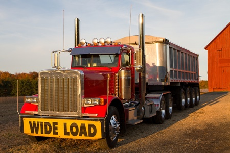 18 wheeler: Tractor trailor with wide load sign is parked in front of a barn in the late afternoon sun.