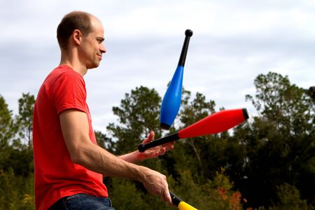 Man tosses and juggles pins in the air at a performance.