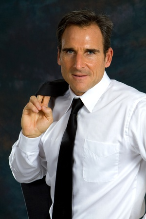 Confident businessman wearing white shirt and tie has his coat draped over shoulder. Stock Photo - 11536770