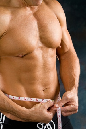 Athletic male uses a tape measure to find out his waist size. Stock Photo - 11536773