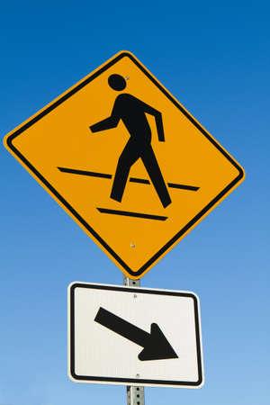 Pedestrians crosswalk sign with arrow against a blue sky. Imagens