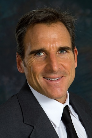 Headshot of middle aged businessman wearing a coat and tie smiling. photo