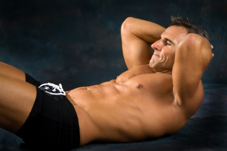 Athletic man performs situp calisthenics for abdominal strengthening.