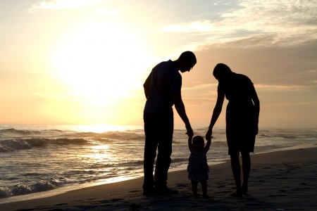 mom and dad: Man and woman, parents of a young child, walk their baby down the beach holding hands on the sand close to sunset as the daughter learns how to walk. Stock Photo