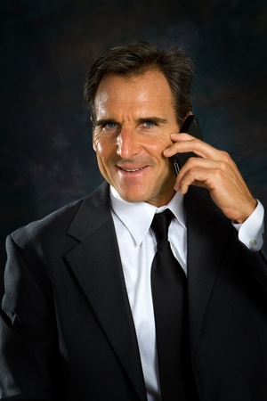 Businessman, white collar worker, in business suit talks on his cell phone. Stock Photo - 11741391