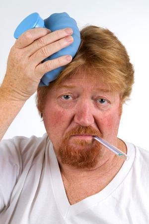chorowity: Chory z termometrem w ustach i termofor na gÅ'owie ma grypÄ™. Zdjęcie Seryjne