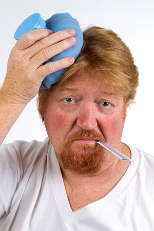 sickly: Sick man with thermometer in mouth and hot water bottle on head has the flu.