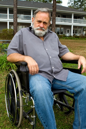 Disabled crippled man sits in his wheelchair in front of his home in the grass. photo