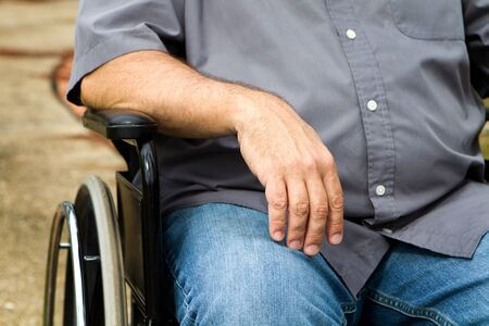 lame: Close up of disabled mans arm and torso as he sits in a wheelchair. Stock Photo