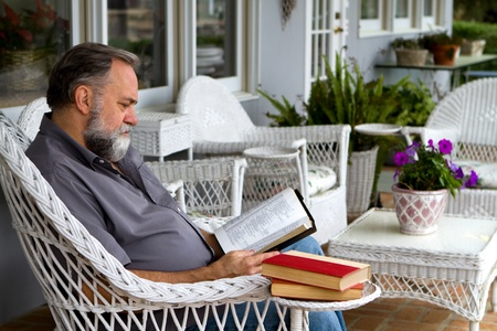 Mature man reads his bible while sitting in a white wicker chair on a porch. photo