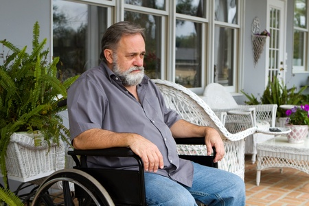 Depressed paraplegic man sits in his wheelchair on the patio.