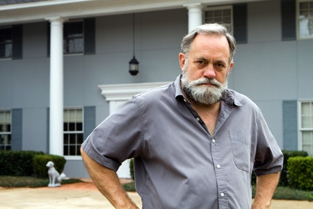 Unhappy homeowner poses in front of his two story columned southern home. Stock Photo - 12474183