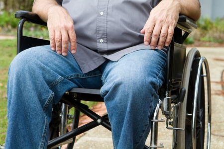 paralysis: Torso and leg view of paraplegic man as he sits outside in his wheelchair.