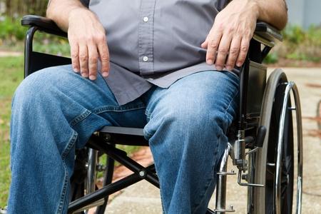 paraplegico: Torso y la pierna de vista parapl�jico como �l se sienta afuera en su silla de ruedas.