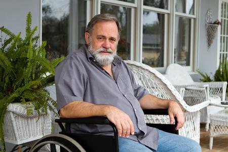 Disabled paraplegic man sits depressed in his wheelchair posing on the porch. Standard-Bild