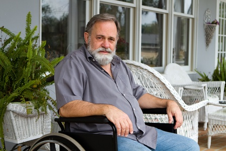 Disabled paraplegic man sits depressed in his wheelchair posing on the porch. Stock Photo