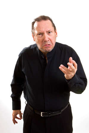 complaining: Grumpy old man dressed in black stretches out his hand with a look of contempt and anger. Stock Photo