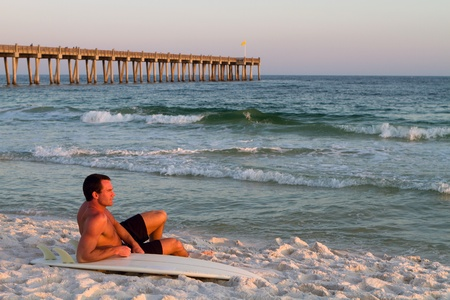 Young handsome adult surfer sits on the beach leaning on his surfboard with a pier in the background on Pensacola Beach, Florida. Stock Photo - 12958536